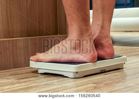 Low Section Of people Standing On Weighing Scale