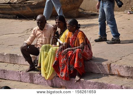 VARANASI, UTTAR PRADESH INDIA - FEBRUARY 17, 2016 - Three unidentified indian people with colorful dresses sitting on the ghats