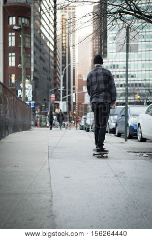 Full back figure of a skateboarder cruising down city street before sunset. Photographed in New York City in Feb 2016.