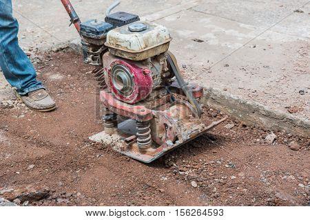 Worker reversible plate compactor on a roadwork site. .Repair cracked Sidewalk