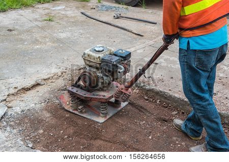 Worker reversible plate compactor on a roadwork site. .Repair cracked Sidewalk