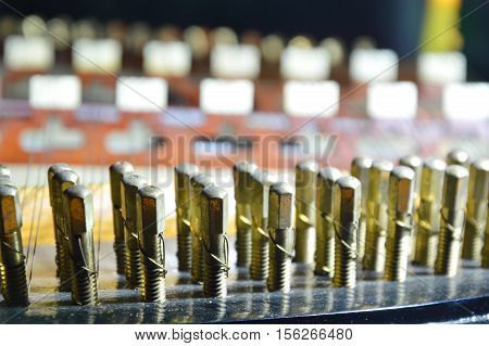 close up of dulcimer brass rivets in the night