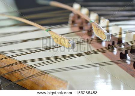 close up of dulcimer string and wooden bat