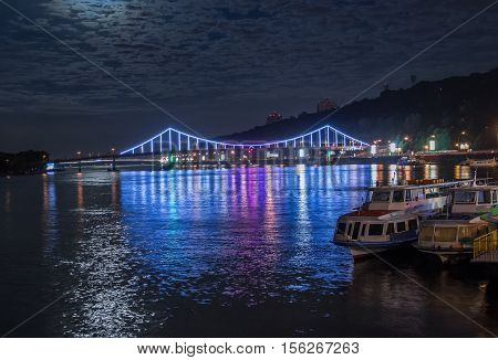 Glowing multicoloured city bridge above river and boats at quay at night