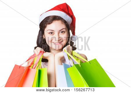 Happy smiling beautiful woman wearing chirstmas hat holding colorful shopping bags on isolated white background