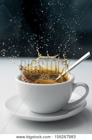 Splash of coffee in white cup abstract background.