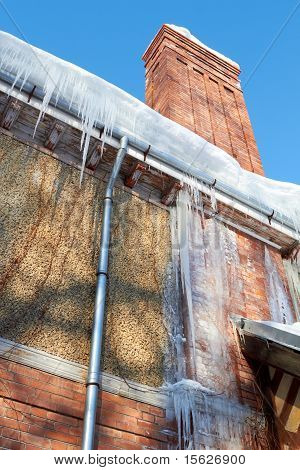 Icicles Hanging From A Drainpipe On A rural House