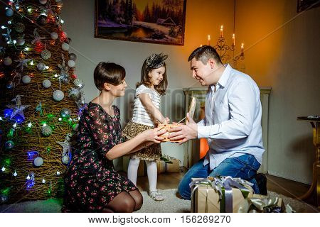 Mom and father give a small child a Christmas gift on the Christmas tree background. Christmas presents.