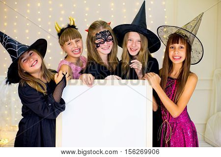Group Of Teenagers Wearing Halloween Costumes Posing With White