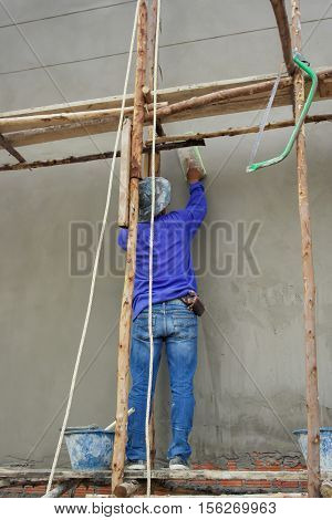 Workman plaster at construction site,Plaster concrete worker at wall of house construction,Building construction site