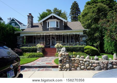 HARBOR SPRINGS, MICHIGAN / UNITED STATES - AUGUST 3, 2016: An elegant stone wall stands in front of a charming house made of stone and brick, across from the Zorn Park Beach in Harbor Springs.
