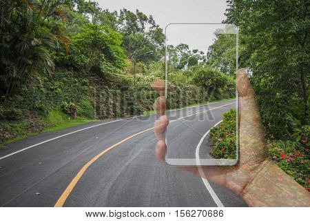 Double exposure woman hand holding,using and touch smart phone,Image of road and tree for the operator advertisement and copy space.