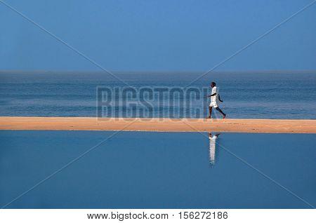 GOA INDIA - NOVEMBER 27 2007: Unidentified man walks on the beach on a bright morning