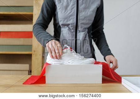 Close Up Of Female Hands Packing Sporting Goods. Sports Shoes. Gift.