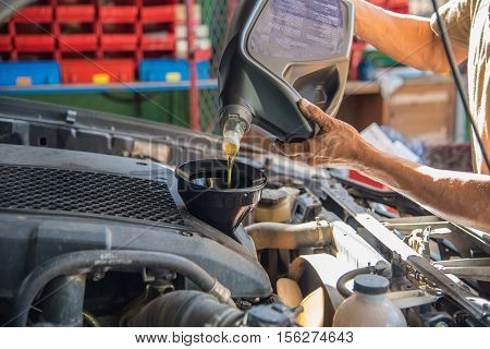 Car maintenance servicing mechanic pouring new oil lubricant into the car engine, A mechanic pours fresh oil into a car engine as part of its maintenance