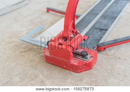 Industrial tiler builder worker working with floor tile cutting equipment at repair renovation work,Worker working on laying of porcelain tiles