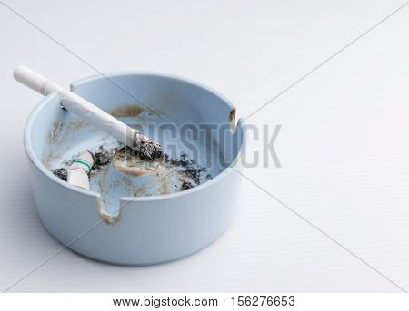 Cigarette in ashtray on a white background.