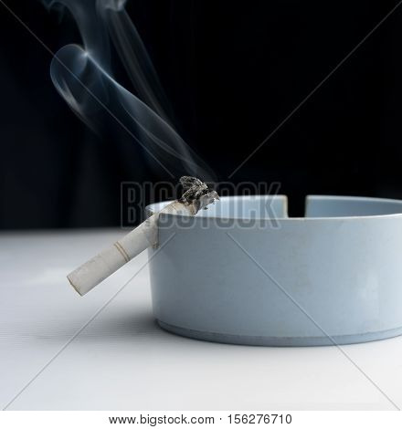 Cigarette in ashtray with abstract smoke .