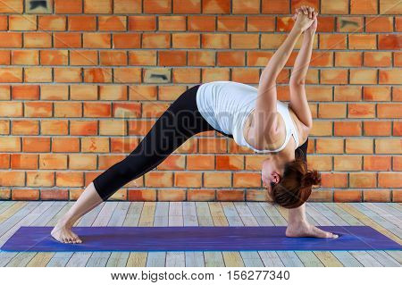 woman yoga exercices fitness sport training and lifestyle concept - smiling woman stretching leg on mat in gym
