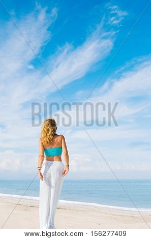 Outdoor summer portrait of young pretty woman looking to the ocean at tropical beach,