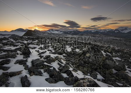 Stone field covered with snow on Laddebakte top with beautiful vibrant sunset Sweden poster