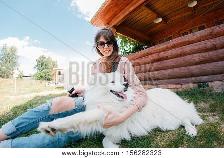 young stylish hipster woman girl playing white kid-skin dog in country side, village wood house, cool outfit, romantic mood, having fun, ripped jeans,