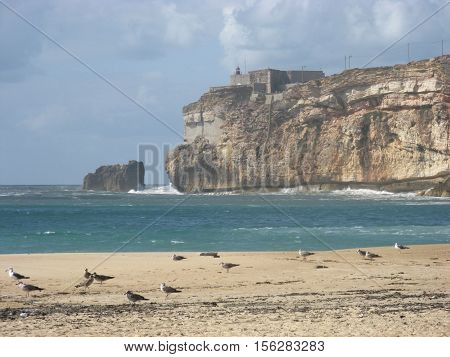 Abandoned beach and rocky promontory in Nazare in autumn, Portugal