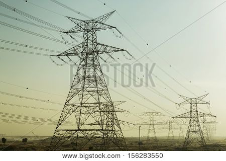 High voltage power lines in Dubai. Voltage electricity pylons in the desert.