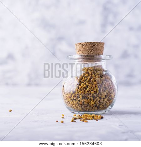 Flower honey bee pollen in a glass jar for storage of small gray light background. The concept of natural organic food. Super food. selective focus