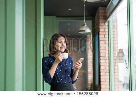 Beautiful cute asian young businesswoman in the cafe using mobile phone and drinking coffee smiling