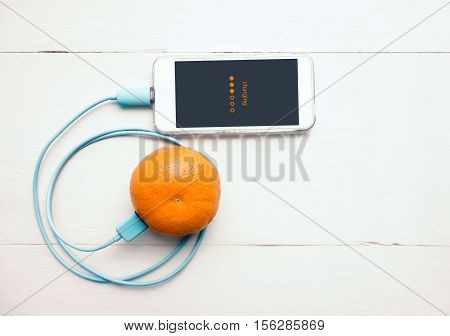 Smartphone Charging Battery From Orange Fruit, Smart And Eco - Friendly To Charge Smartphone Concept