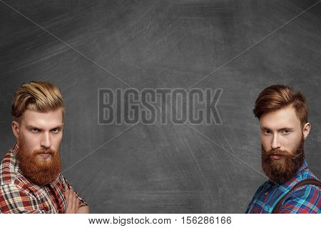 Two courageous brutal hipster men with stylish beards in checkered shirts posing isolated in bottom right-hand and left-hand corners on blank chalkboard looking at camera with severe angry expression