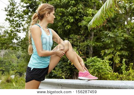 Attractive Blonde Female Jogger Wearing Pink Sneakers Examining Her Leg For Injury, Resting Her Foot