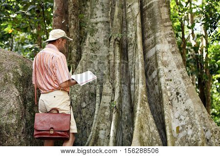 Nature And Environmental Protection And Conservation. Botanist In Hat And Shirt Reading Notes In His