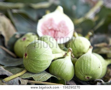 Cut figs on a fig leaf on a background