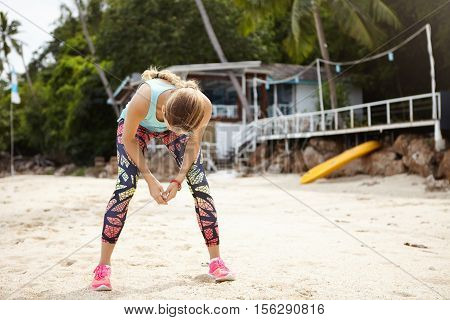 Exhausted Blonde Sportswoman In Colorful Leggings And Pink Sneakers Standing On Beach Sand With Hand