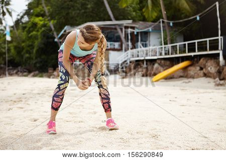 Caucasian Woman Jogger In Sportswear Having Rest After Long Run, Leaning Over, Placing Elbows On Her