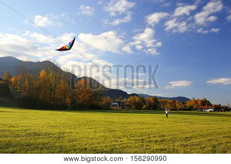 girl is playing with a kite on an autumn field