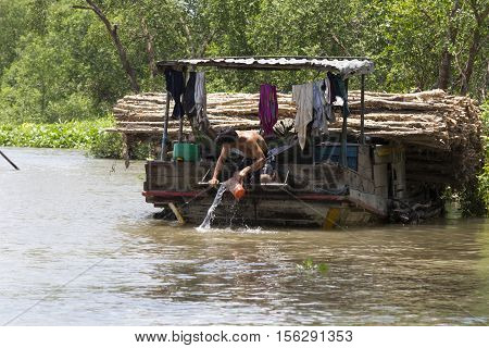 Small Boat With A Man Washing Himself