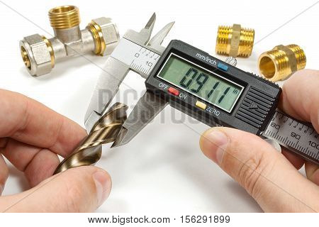 Measurement diameter of drill a digital caliper in the master's hands on a white background