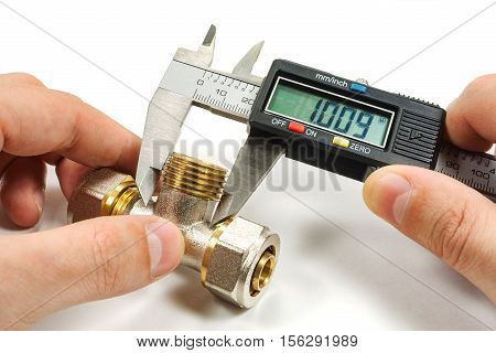 Measurement of plumbing fitting with digital caliper in the master's hand