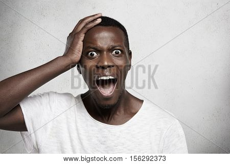 Headshot Of Terrified Young African Employee In White T-shirt Holding Hand On His Head And Screaming