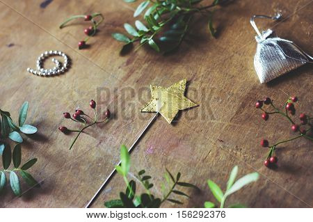 Magic star wand on wooden table surrounded by tiny gifts or plants.