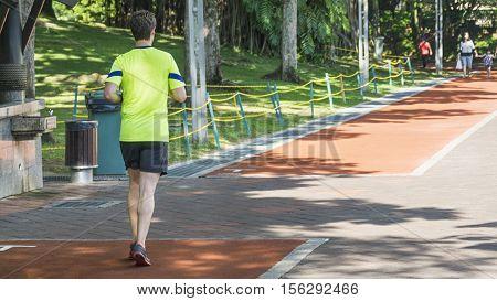 Man is running in the running way in the garden park.
