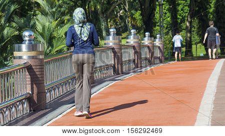 Girl is running in the running way in the garden park.