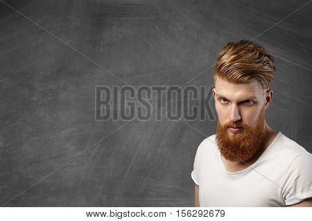 Attractive Redhead Hipster Man With Stylish Haircut And Thick Beard Posing Against Blank Blackboard