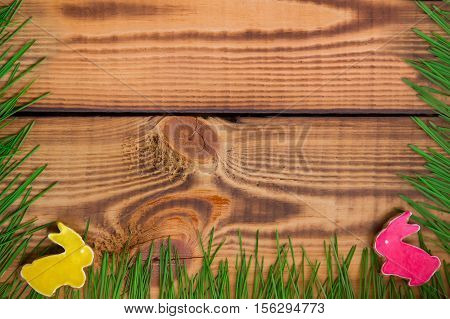 Happy easter. Easter background. Summer background. Easter cookies. Gingerbread in the form of crimson and yellow Easter rabbits on green grass on a background of brown wooden desk. Free space