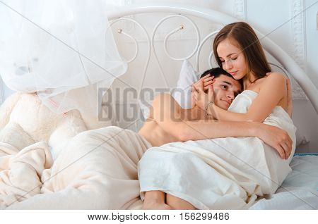 sweet young couple in love hugging in the bed