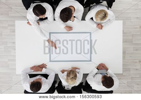 Business team sitting at table and pointing finger to blank paper in office