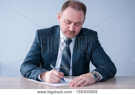 Man in business suit writing on a sheet of paper